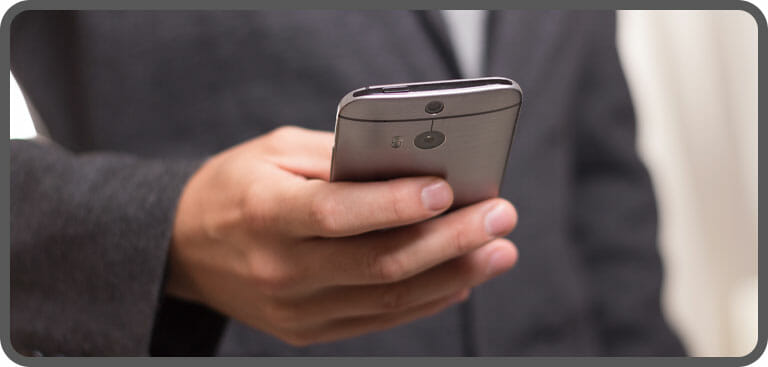 Close up of employee using a a mobile phone to make remote phone call via hosted phone system
