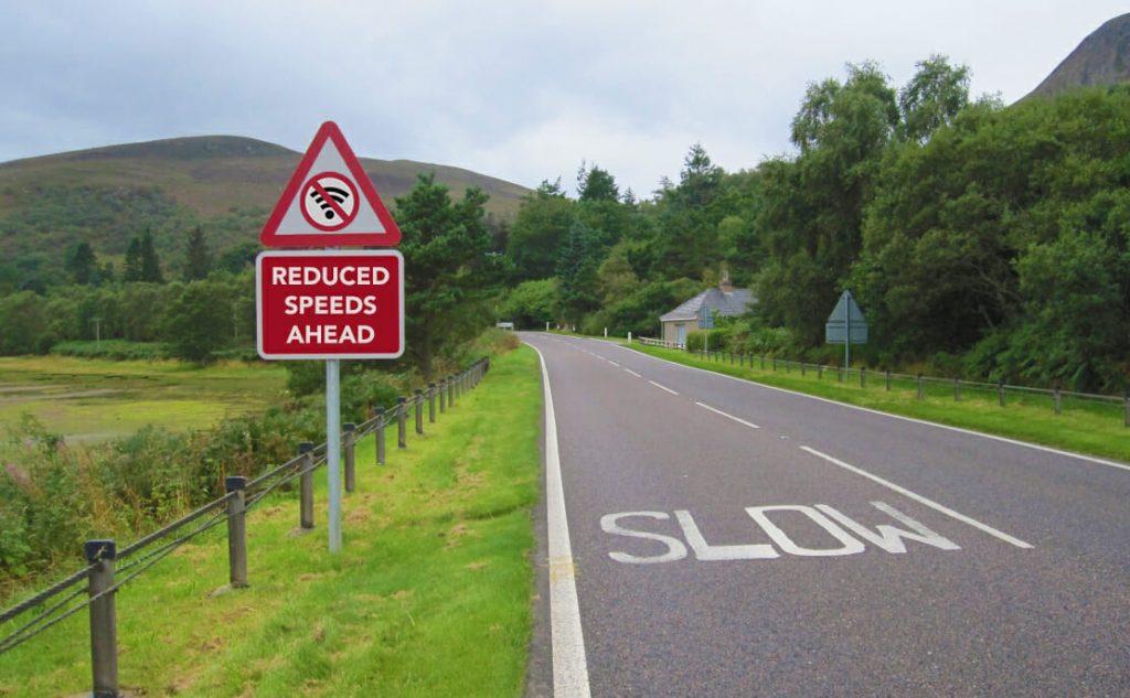 A rural road sign warning of slow broadband speeds
