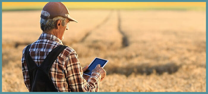 A farmer using a tablet device to connect to the internet in a rural field using a WiFi broadband connection
