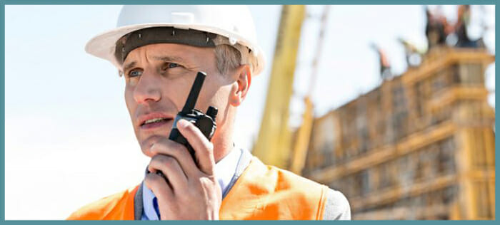Construction worker using walkie-talkie radio for communication