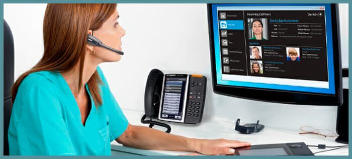 Dental office receptionist making a hands-free call using an IP-based phone system