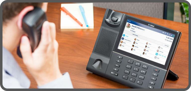 Employee using hosted phone system to make call via VoIP handset
