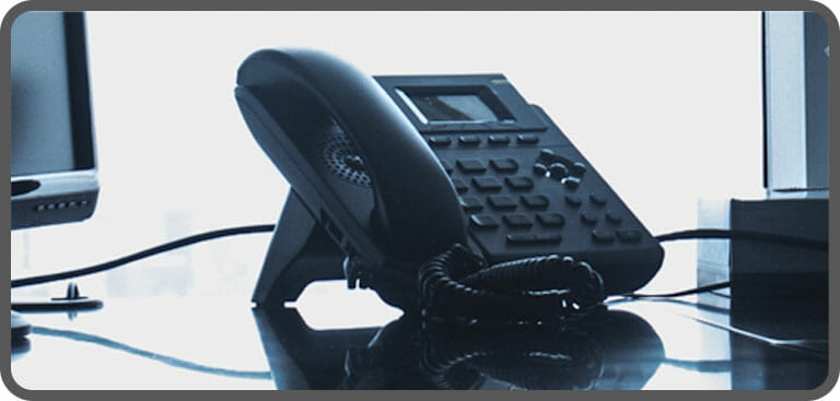 Black VoIP phone handset on desk