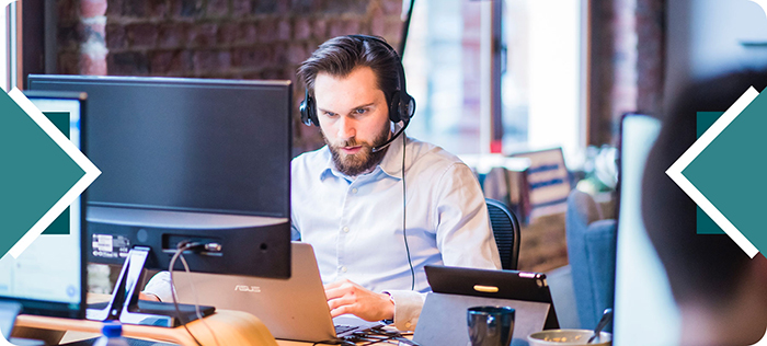 Male employee working at desk wearing VoIP phone headset