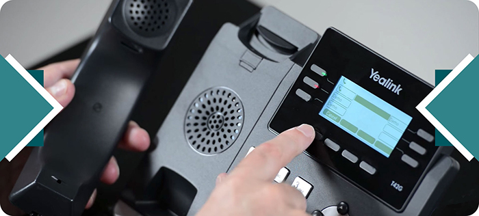 Hand pushing buttons on VoIP phone keypad